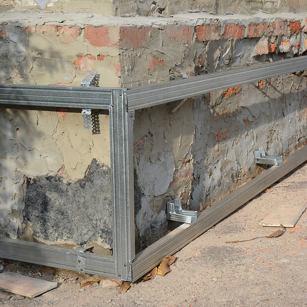 house foundation wall repair and renovation with installing on frame metal sheets for waterproofing