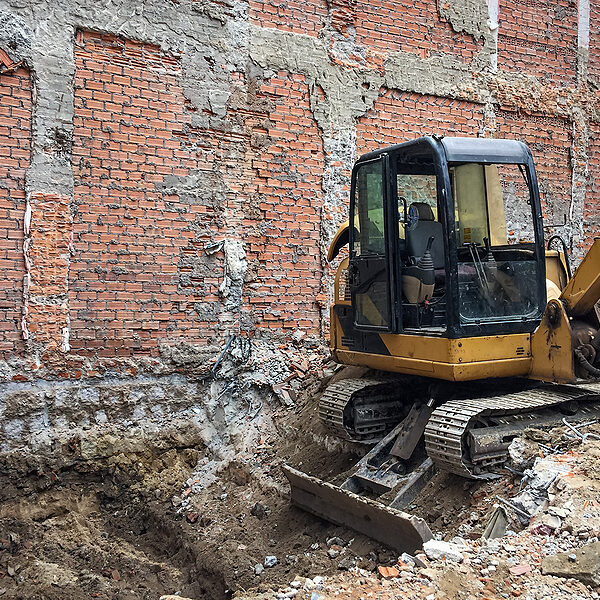 small excavator at construction site. dismantling of an old house, rebuilding with heavy construction equipment